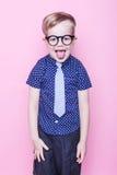 Muchacho elegante en camisa y vidrios con sonrisa grande Escuela pre-entrenamiento Moda Retrato del estudio sobre fondo rosado fotos de archivo libres de regalías