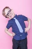 Muchacho elegante en camisa y vidrios con sonrisa grande Escuela pre-entrenamiento Moda Retrato del estudio sobre fondo rosado foto de archivo