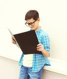 Muchacho elegante hermoso del adolescente en los vidrios que miran o libro de lectura Foto de archivo libre de regalías