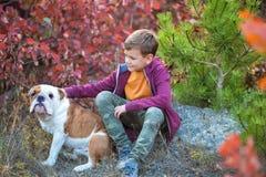 Muchacho elegante hermoso lindo que goza del parque colorido del otoño con su perro inglés rojo y blanco del mejor amigo del toro Foto de archivo libre de regalías