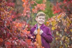 Muchacho elegante hermoso lindo que goza del parque colorido del otoño con su perro inglés rojo y blanco del mejor amigo del toro Fotos de archivo