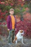 Muchacho elegante hermoso lindo que goza del parque colorido del otoño con su perro inglés rojo y blanco del mejor amigo del toro Fotografía de archivo
