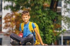Muchacho elegante lindo con la mochila que se sienta al aire libre después de escuela imágenes de archivo libres de regalías