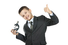 Muchacho elegante lindo en traje y lazo con un microscopio Foto de archivo libre de regalías