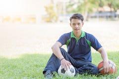 Muchacho elegante que se sienta con fútbol y baloncesto en hierba verde Imagenes de archivo