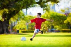 Muchacho emocionado joven que golpea la bola con el pie en la hierba Foto de archivo
