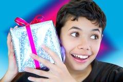 Muchacho emocionado llevando a cabo para arriba envuelto un regalo de Navidad Imagenes de archivo