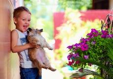 Muchacho emocionado que sostiene el perrito querido Foto de archivo
