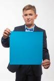 Muchacho emocional del adolescente rubio en un traje azul con una hoja de papel azul para las notas Imagen de archivo libre de regalías