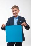 Muchacho emocional del adolescente rubio en un traje azul con una hoja de papel azul para las notas Foto de archivo