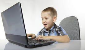 Muchacho emocional del apego del ordenador con el ordenador portátil Imágenes de archivo libres de regalías