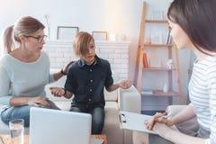 Muchacho emocional que gesticula mientras que habla con el psicoterapeuta de sexo femenino Foto de archivo libre de regalías