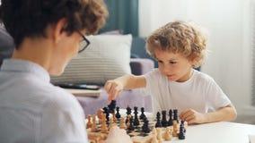 Muchacho emocional que juega a ajedrez con los pedazos móviles de la mamá a bordo y la sonrisa metrajes