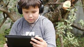 Muchacho en auriculares con el panel táctil al aire libre almacen de metraje de vídeo