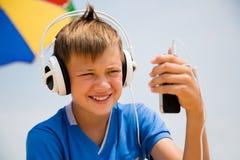 Muchacho en auriculares con su smartphone al aire libre Imagen de archivo libre de regalías