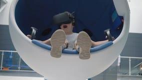 Muchacho en auriculares de la realidad virtual en una silla interactiva m?vil metrajes
