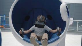 Muchacho en auriculares de la realidad virtual en una silla interactiva m?vil almacen de video