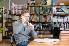 Muchacho en biblioteca que habla en el teléfono Foto de archivo libre de regalías