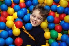 Muchacho en bolas multicoloras Foto de archivo libre de regalías