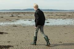 Muchacho en botas altas y chaqueta que caminan en la playa Imágenes de archivo libres de regalías