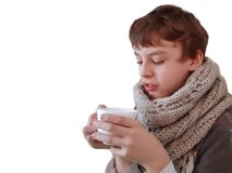 Muchacho en bufanda hecha punto gris con la taza en las manos en el fondo blanco foto de archivo libre de regalías