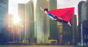 Muchacho en cabo del super héroe y máscara que vuela sobre ciudad Imágenes de archivo libres de regalías