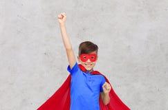 Muchacho en cabo rojo del super héroe y máscara que muestra los puños Imagen de archivo