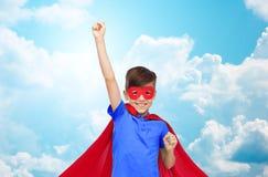 Muchacho en cabo rojo del super héroe y máscara que muestra los puños Fotografía de archivo