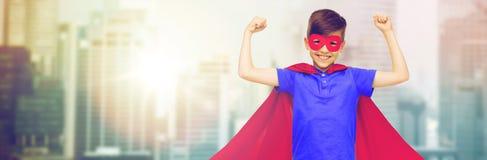 Muchacho en cabo rojo del super héroe y máscara que muestra los puños Imagen de archivo libre de regalías