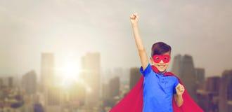 Muchacho en cabo rojo del super héroe y máscara que muestra los puños Fotos de archivo