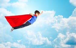 Muchacho en cabo rojo del super héroe y máscara que vuela sobre el cielo Foto de archivo libre de regalías