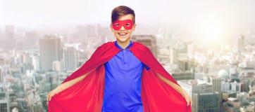 Muchacho en cabo rojo del super héroe y máscara sobre ciudad Imagen de archivo libre de regalías
