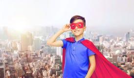 Muchacho en cabo rojo del super héroe y máscara sobre ciudad Fotografía de archivo libre de regalías