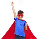 Muchacho en cabo rojo del superhéroe y máscara que muestra los puños Imágenes de archivo libres de regalías