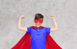 Muchacho en cabo rojo del superhéroe y máscara que muestra los puños Fotos de archivo