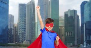Muchacho en cabo rojo del superhéroe y máscara que muestra los puños Fotos de archivo libres de regalías