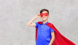 Muchacho en cabo y máscara rojos del super héroe Fotos de archivo libres de regalías