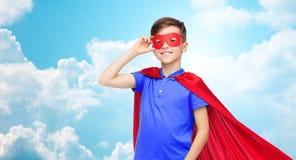 Muchacho en cabo y máscara rojos del super héroe Imágenes de archivo libres de regalías