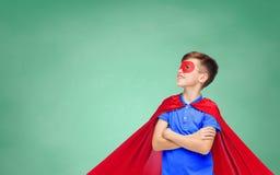 Muchacho en cabo y máscara rojos del superhéroe Foto de archivo libre de regalías