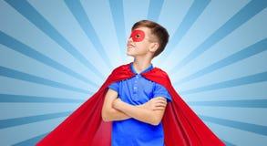 Muchacho en cabo y máscara rojos del superhéroe Fotos de archivo