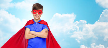 Muchacho en cabo y máscara rojos del superhéroe Imagenes de archivo
