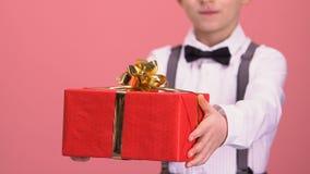 Muchacho en caja de regalo de la demostración del traje a la cámara, a la celebración y a la enhorabuena, día de fiesta metrajes