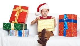 Muchacho en cajas de regalo abiertas de santa del sombrero rojo del ayudante - concepto del día de fiesta de la Navidad Imágenes de archivo libres de regalías