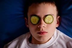 Muchacho en cama con las rebanadas del pepino sobre sus ojos Fotos de archivo libres de regalías
