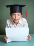 Muchacho en casquillo de la graduación con la hoja del Libro Blanco en manos Foto de archivo libre de regalías