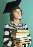 Muchacho en casquillo de la graduación con la pila del libro Foto de archivo