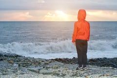 Muchacho en chaqueta roja con la capilla que se coloca en la playa Puesta del sol y ondas Fotos de archivo libres de regalías