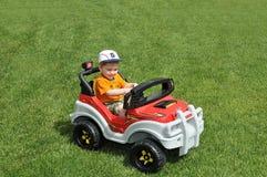 Muchacho en coche del juguete en hierba Foto de archivo