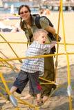 Muchacho en cuerdas amarillas con la mama Imagen de archivo libre de regalías