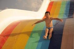 Muchacho en diapositiva de agua colorida Imágenes de archivo libres de regalías